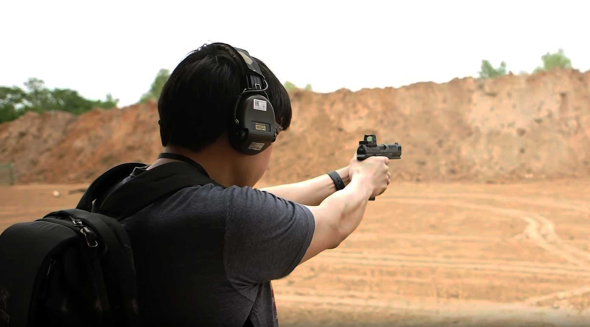 pistol shooter using a red dot sight while training at the range