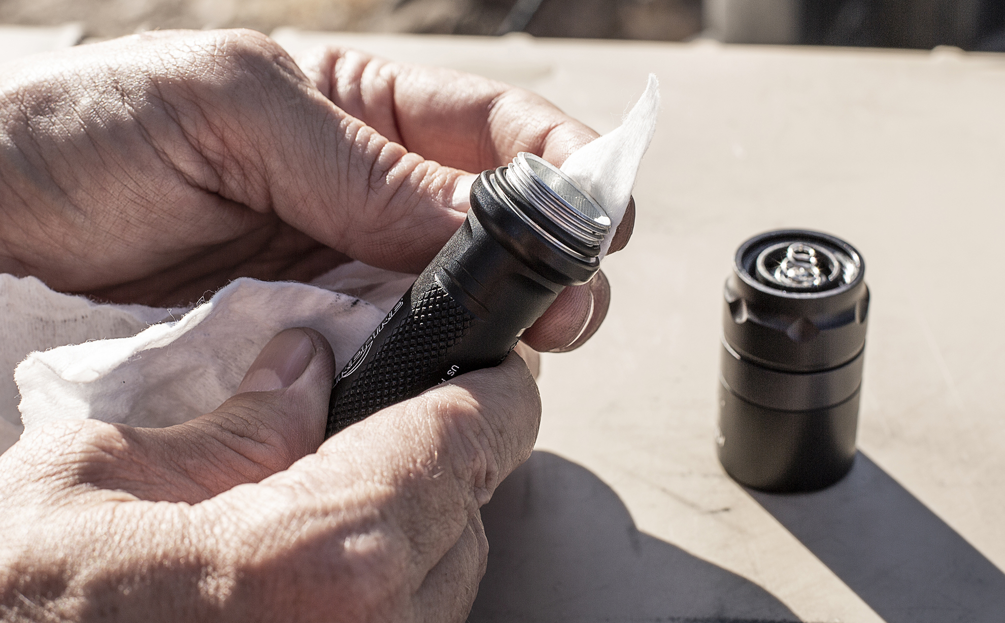SureFire flashlight tailcap being cleaned